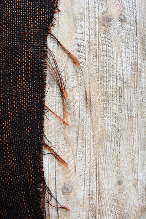 The texture of the fabric large weave, on the wooden table. Brown with place for your text