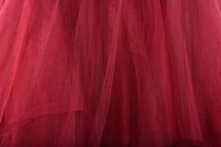 Red fabric texture background. The skirt is made of tulle Zdjęcie Seryjne