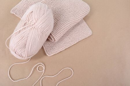 A skein of wool and a knitted scarf of beige thread. Zdjęcie Seryjne