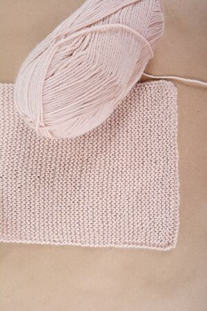 Hobby. Knitting. A skein of wool and a knitted scarf of beige thread. Фото со стока