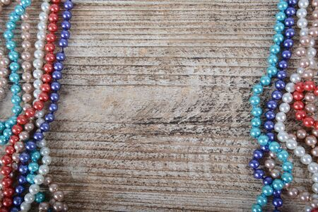 Frame of colorful beads on textured wooden background