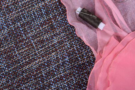 Pink silk fabric and bobbin threads on a gray background Zdjęcie Seryjne
