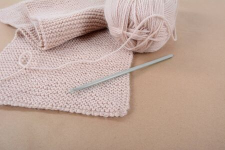 Hobby. Knitting. A skein of wool and a knitted scarf of beige thread. Zdjęcie Seryjne