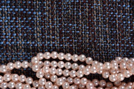 pearl necklace on gray fabric background