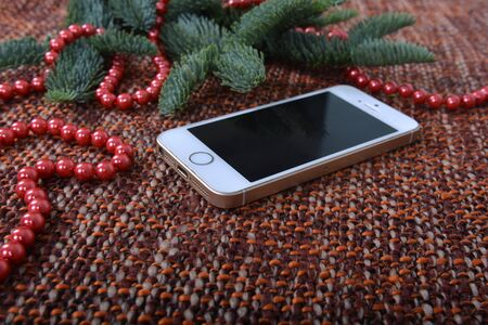Christmas decor and smartphone on fabric brown background.