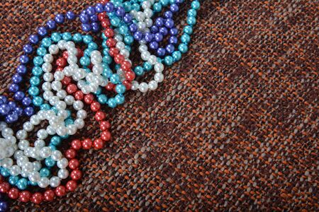 pearl necklace on brown fabric background