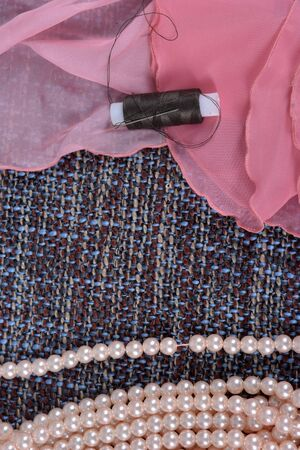 Pearl necklace and bobbin threads on a gray fabric background