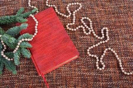 Holiday decoration with pearls, pearl beads, fir-tree branches and red book.