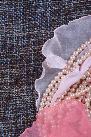 Pearl necklace and gently pink fabric on the gray background Фото со стока