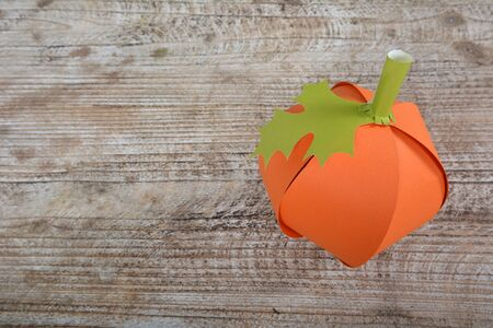 Pumpkin made of hand-made colored paper on the background of a wooden table
