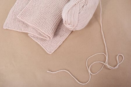 A skein of wool and a knitted scarf of beige thread. Фото со стока