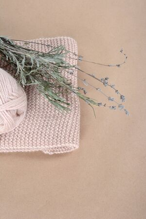 Knitted biege scarf and a bunch of lavender.. Still-life handmade