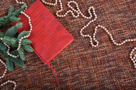 Holiday decoration with pearls, pearl beads, fir-tree branches and red book. Background, copy space. Stockfoto