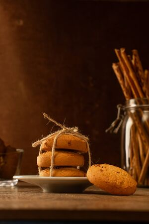 Oatmeal cookies and chopsticks. Still life in vintage style. Brown background