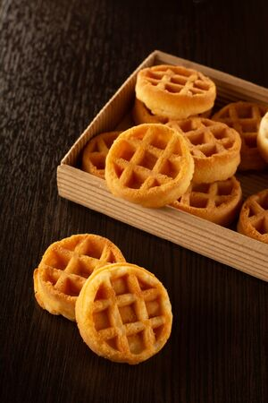 Waffle round-shaped biscuits on the table in a box