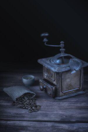 Vintage coffee grinder and bag of coffee beans. Moonlight style still life. Zdjęcie Seryjne