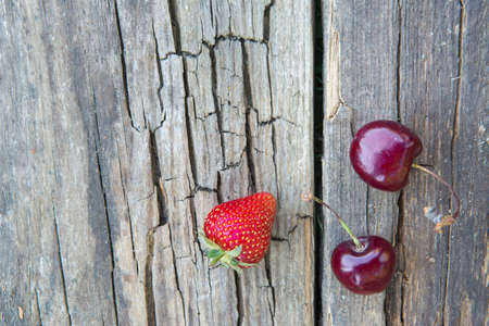 Strawberries and cherries on the surface of the old wooden table