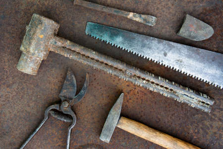 Ancient rusty tools on a metal surface. Steampunk style. Фото со стока