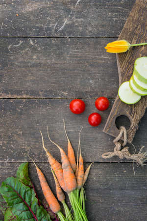 Fresh vegetables with leaves on the old wooden cutting board. Rustic style