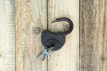 Opened old rusty lock with several keys lying near. Copy space. Looking for problem solution concept in steampunk style