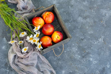 Bouquet of wild flowers chamomile with fruits of nectarines in a wooden box Фото со стока