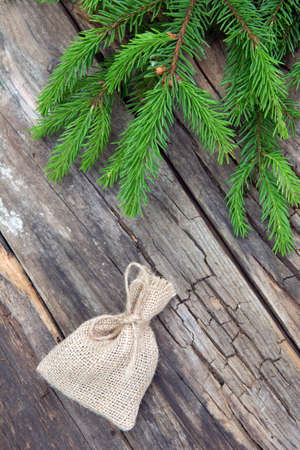 Small bag of burlap and branch green spruce on background of a wooden old table