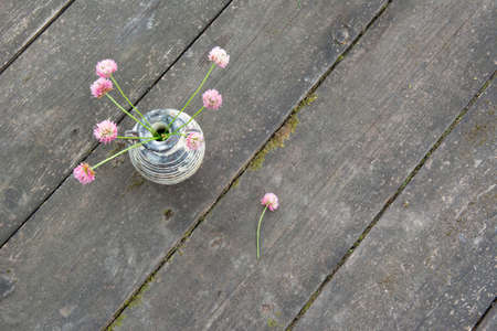 Bouquet of clover in a small vase on an old wooden table. Rural style