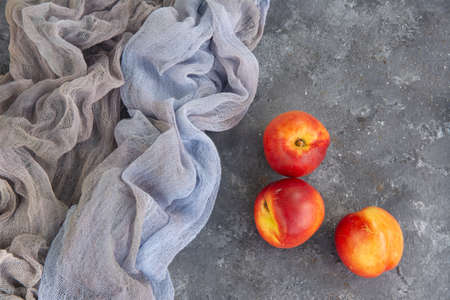 Fresh peaches and draping on the surface of the texture table. Фото со стока