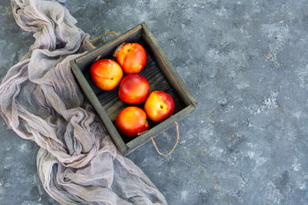 Fruits of nectarines peaches in a wooden box. Rustic style. Copy space.