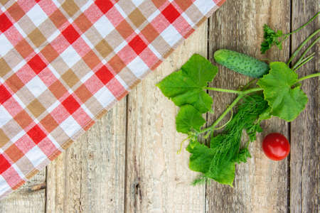 Fresh vegetables with leaves, checkered tablecloth on a wooden table. Rustic style. Copy space Фото со стока