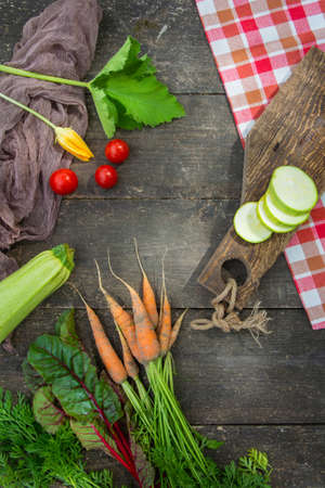 Fresh vegetables with leaves and flower on the old wooden table. Country style Фото со стока