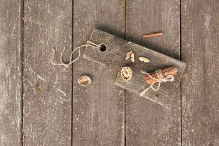 Pieces of walnut cinnamon sticks on a wooden board, photo rustic style