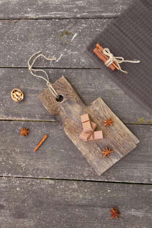 Pieces of chocolate, cinnamon sticks and stars anise on a wooden board, photo rustic style