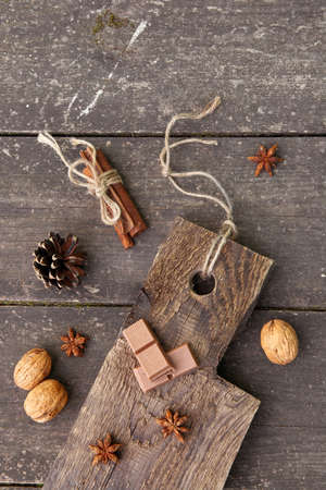 Pieces of chocolate, cinnamon sticks and star anise on a wooden board, photo rusticstyle Фото со стока