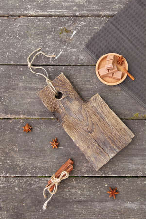 Pieces of chocolate, cinnamon sticks and star anise on a wooden board, photo rustic style. Copy space