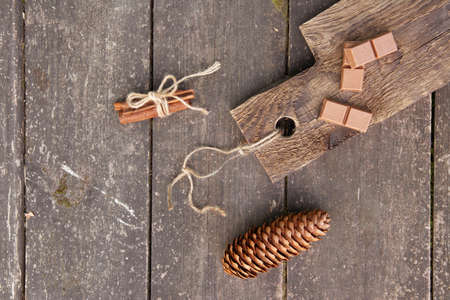 Pieces of chocolate, cinnamon sticks and cone on a wooden board, photo rustic style