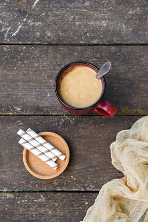 A cup of coffee, pieces of chocolate bars and sticks against a wooden table. Dessert. Copy space