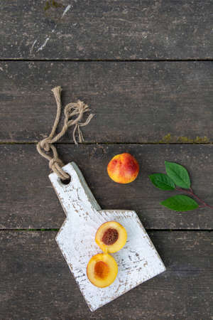 Fresh peaches with leaves on the wooden table close-up. Copy space