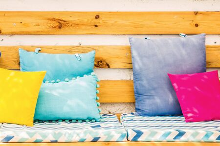 Close up pillows on an outdoor patio chair, with a blue striped cushioned bench. Stock Photo