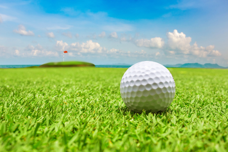 Golf ball on green grass with the ocean background