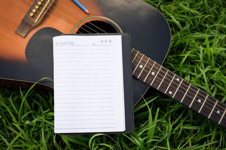 Paper for writing songs with a guitar on the lawn.