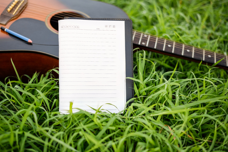 Paper for writing songs with a guitar on the lawn. - Standard-Bild