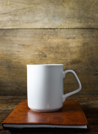 cup of coffee and book on old wood background