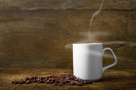 Cup of coffee with smoke and coffee beans on old wooden background Lizenzfreie Bilder