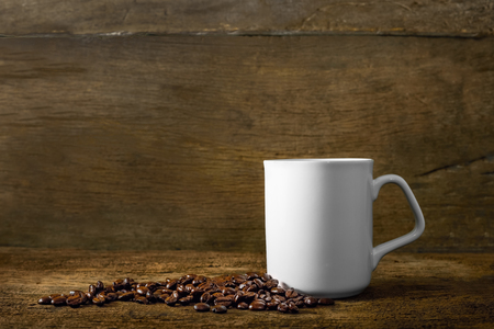 Coffee cup and coffee beans on old wooden background Standard-Bild