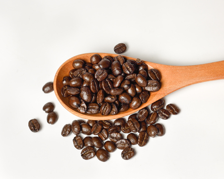 Coffee in wooden scoop on white background.