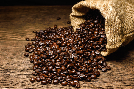 Coffee beans in coffee bag made from burlap on wooden surface.