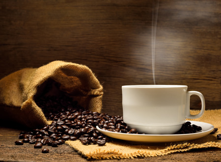Cup of coffee and coffee beans with smoke on old wooden. Stock Photo