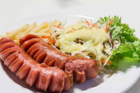 sausage grill with salad and french flies on white dish Standard-Bild