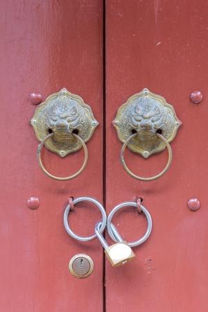 antique lion head knocker on the door with key lock photo